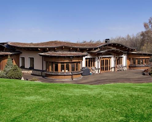 Átriový dům se zelenou střechou.