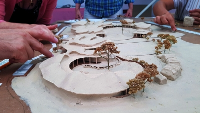 Detailní práce při tvarování plynulosti střech mateřské školky. Tam kde je uvnitř třída, je na střeše viditelné plynulé vyvýšení. Směrem k jihu jsou ve střechách okna s přesahem střechy. Směrem do vnitřní zahrady je zastřešená pasáž, která umožnuje komunikaci mezi třídami a přistiňuje velká jižní okna do tříd v parteru.