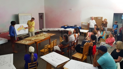 Final presentation of Oldřich Hozman at the school in Reno. Models and an architectural study of the school campus are displayed on tables.